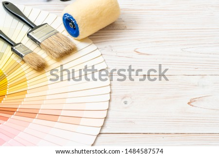 sample colors catalogue pantone or colour swatches book with paint roller brush