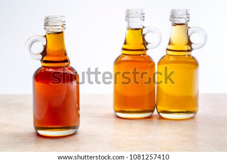 sampler of pure maple syrup (golden, amber and gold) - three small glass bottles on a ceramic background #1081257410