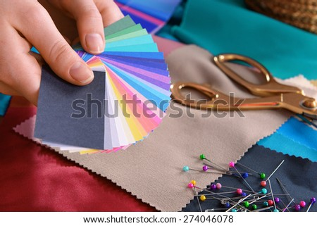 Samples of colorful fabric in female hands, closeup #274046078