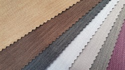 samples of fabric for interior upholstery or drapery works in earth tone color. swatch of zigzag pattern fabric.