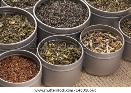 samples of loose leaf green, red, black and herbal tea in metal cans on canvas background