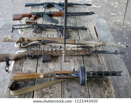 Samples of Soviet automatic weapons of the second world war. Machine guns and machine guns on a wooden table outside on a summer day.
