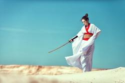 Samurai Girl with a sword in the desert.