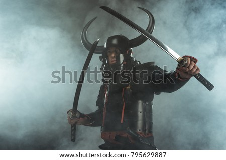 samurai in traditional armor with dual katana swords in defence position on dark background with smoke