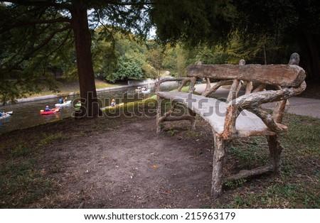 San Antonio, Texas, USA - Circa July, 2014 : Park bench with Canoeists paddling circa July, 2014 on the San Antonio River, San Antonio, Texas.