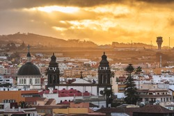 San Cristóbal de La Laguna, and its Cathedral during the sunset. Orange sky, and the buildings cutting the horizon in front of the airport.