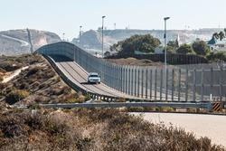San Diego, California and Tijuana, Mexico international border wall with border patrol vehicle.