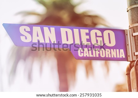 San Diego California Street Sign. A street sign marking San Diego, California. Backed by a palm tree with a sunset flare.