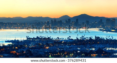 San Diego downtown skyline at sunrise with boat in harbor.