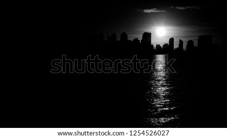 San Diego skyline in monochrome black and white with beautiful contours of down town cityscape with burning sun reflecting in sea water.  More similar content is found in my portfolio.  #1254526027