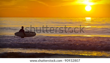 San Diego Surfer with Surf Board Wading into Ocean During Sunset