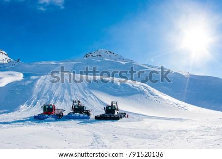 San Domenico, Varzo, Alps, Italy, three snowcats on the ski slopes prepare the slopes for skiers early in the morning, sunny day #791520136