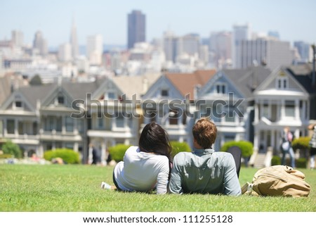 San Francisco - Alamo Square people. Couple in Alamo Park by the Painted Ladies, The Seven Sisters, San Francisco, California, USA.