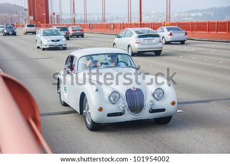 SAN FRANCISCO - APRIL 30: A 1957 Jaguar XK150 fhc is being driven on Golden Gate Bridge during the 2012 California Mille race in San Francisco on April 30, 2012