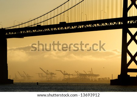 San Francisco Bay bridge and polluting industrial barges  at sunrise