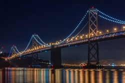 San Francisco Bay Bridge on a clear night, lit up by yellow and blue lights, reflecting of the water in the Bay, long exposure