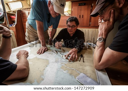 SAN FRANCISCO BAY - FEBRUARY 15: captain and crew study the navigation charts to determine sailing course on February 15, 2013 in San Francisco, California host of the 2013 Americas Cup sailing races.