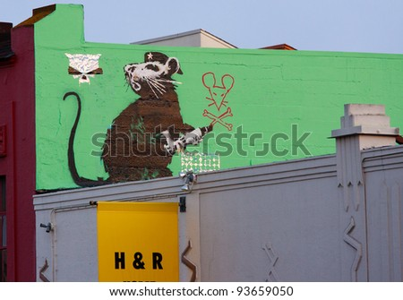 SAN FRANCISCO, CA - CIRCA MAY 2010: Stencil graffiti piece by Banksy on a building on 9th St, circa May 2010 in San Francisco, CA
