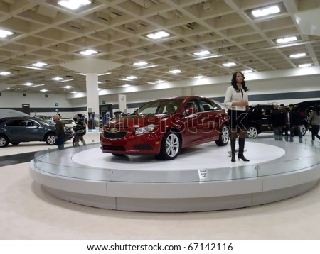 SAN FRANCISCO, CA - NOVEMBER 20: Lady discusses features of the Chevy Cruze on a spinning display platform at the 53rd International Auto Show November 20 2010 San Francisco.