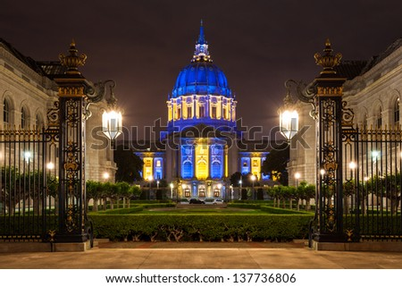San Francisco City Hall in blue and gold light at night.