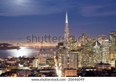 San Francisco financial district at night, with the bay illuminated by the full moon.