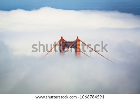 San Francisco Golden Gate Bridge poking through thick fog during the day