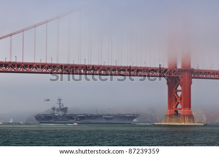 SAN FRANCISCO - OCTOBER 8: Aircraft carrier USS Carl Vinson passes under the Golden Gate Bridge during Fleet Week on October 8, 2011 in San Francisco, USA