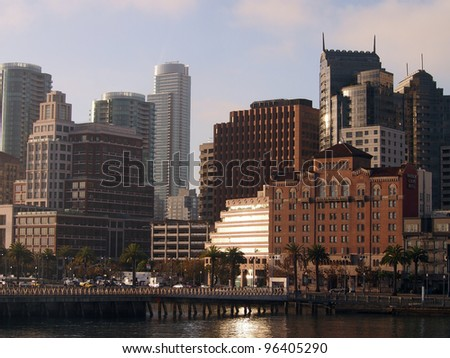 San Francisco Pier and Cityscape as rising sun reflects on buildings on a nice day.