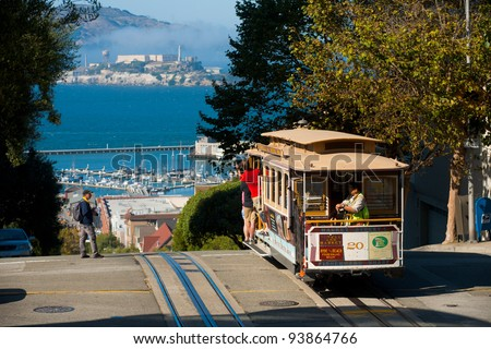 SAN FRANCISCO, USA - SEPT. 21:  Tourists ride the cable car on a sunny day at the top of Hyde Street overlooking Alcatraz in San Francisco September 21, 2011 in San Francisco, USA