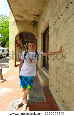 SAN MARINO, ITALY – July, 2014: Man stands on beautiful little streets of San Marino waiting for tourists. Narrow street in old town. San Marino located on Italian peninsula, near Adriatic Sea