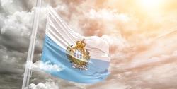 San Marino national flag cloth fabric waving on beautiful grey sky.