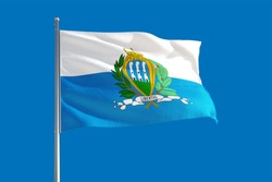 San Marino national flag waving in the wind on a deep blue sky. High quality fabric. International relations concept.