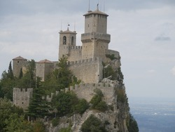 San Marino, the Witches Pass. Closeup on the First Tower perched on a rock overlooking the surrounding area and the sea from the path with the stairway carved into the rock