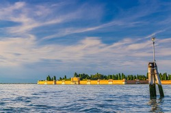 San Michele island in Venetian Lagoon near Venice city with famous cemetery of Isola di San Michele, wooden poles in water, sestiere of Cannaregio, Veneto Region, Northern Italy.