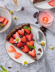 San Valentine Chocolate Raw Tart with strawberries and camomile flowers, served in white desserts plates over grey surface.