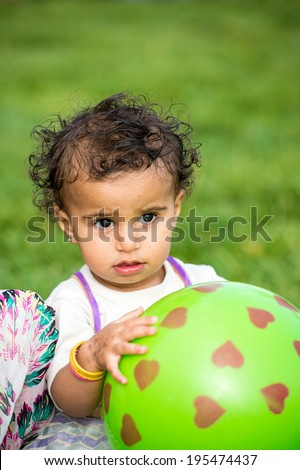SANA\'A, YEMEN - JAN 11, 2014: Unidentified Yemeni little girl plays with a green rubber ball girl in the street in Sana\'a. Children of Yemen grow up without education
