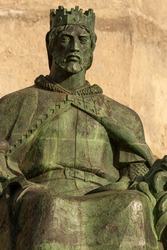 Sancho IV of Castile called the Brave (el Bravo), was the king of Castile, Leon and Galicia. Sitting bronze statue of him is seen in front of historic Castle of Guzman El Bueno in Tarifa, Cadiz Spain