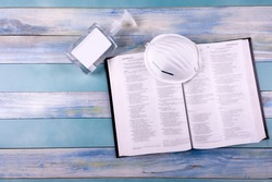 Sanctuary of a church with face mask, hand sanitizer and bible on vintage wood background. Social distance.