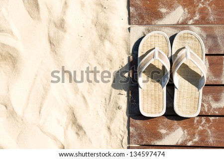 Sand and beige flip flops. Pair of sandals on boardwalk. Walk on sand in bright sunny day, Leisure time at beach. Creative concept of carefree vacations. Popular outdoor activity in summer.