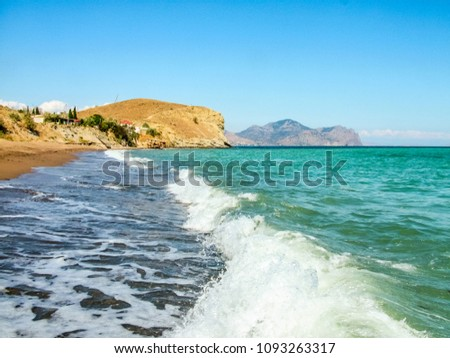 Sand and pebble beach on the Black Sea coast. Crimea. Settlement Sunny Valley (Solnechnaya Dolina). In the background is the ancient extinct volcano Kara-Dag.