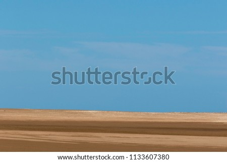Sand and sky background. A simple composition of a beach and blue sky  #1133607380