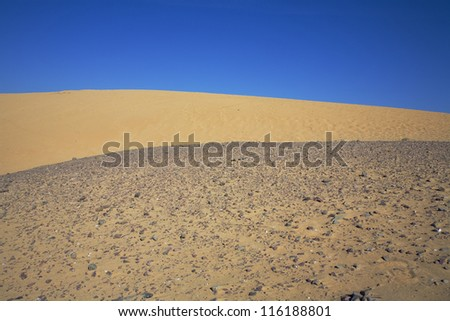 sand and stone dunes under a blue sky