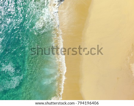 Sand beach aerial, top view of a beautiful sandy beach aerial shot with the blue waves rolling into the shore, some rocks present #794196406