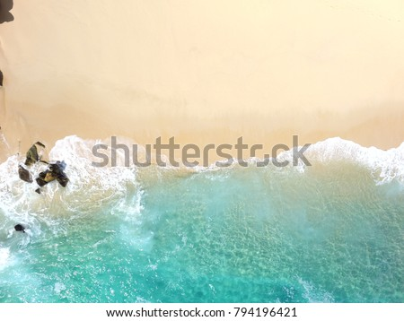 Sand beach aerial, top view of a beautiful sandy beach aerial shot with the blue waves rolling into the shore, some rocks present - Shutterstock ID 794196421