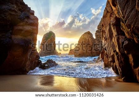 Sand beach among rocks on evening sunset. Ursa Beach near Cape Roca (Cabo da Roca) at Atlantic Ocean coast in Portugal. Summer landscape. Foto stock ©