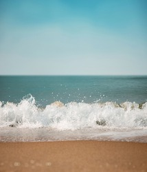 Sand Beach and Hard Wave on Summer Sunny Day. Blue Ocean and Sky as background. Low angle View. Focus on Water Ripple Swash