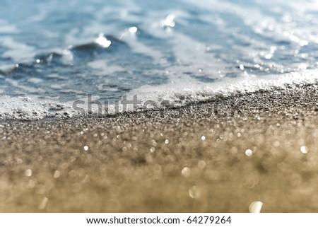Sand beach and sea foam macro with narrow focus background