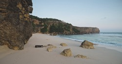 Sand beach at rock ocean coast wavesaerial view. Nobody tropic nature seascape of cliff seashore with boulder at sandy sea bay. Summer tropic landscape of Sumba Island, Indonesia at drone shot