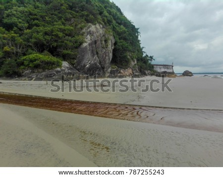 Sand beach, creek, and fortress on a cloudy day in the island Ilha do Mel, Brazil