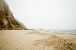 Sand beach, Morro rock on an overcast foggy day, California Coastline, Morro Bay State Park